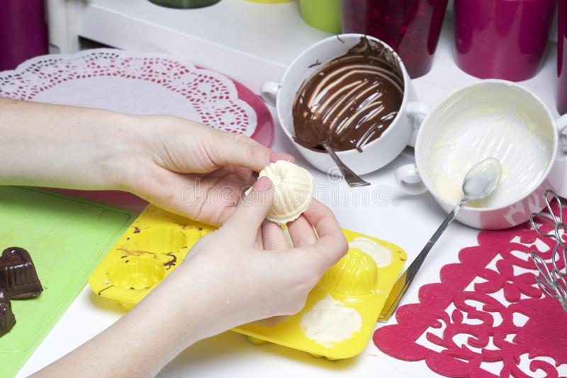 Woman pulls out of the silicone form candy. Cooking sweets with coconut and condensed milk. In a glaze of white and black. Chocolate stock photography