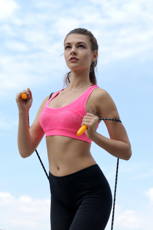 Woman pulls a skipping rope around her body. Girl pulls a skipping rope around her body against the blue sky. She is wearing a pink shirt and black leggings royalty free stock image