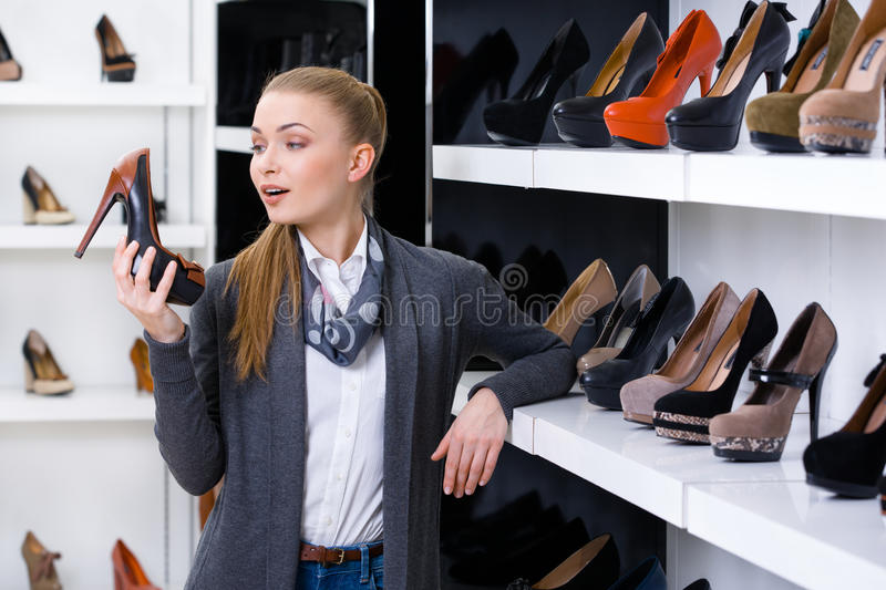 Woman with pump in hand chooses shoes royalty free stock images