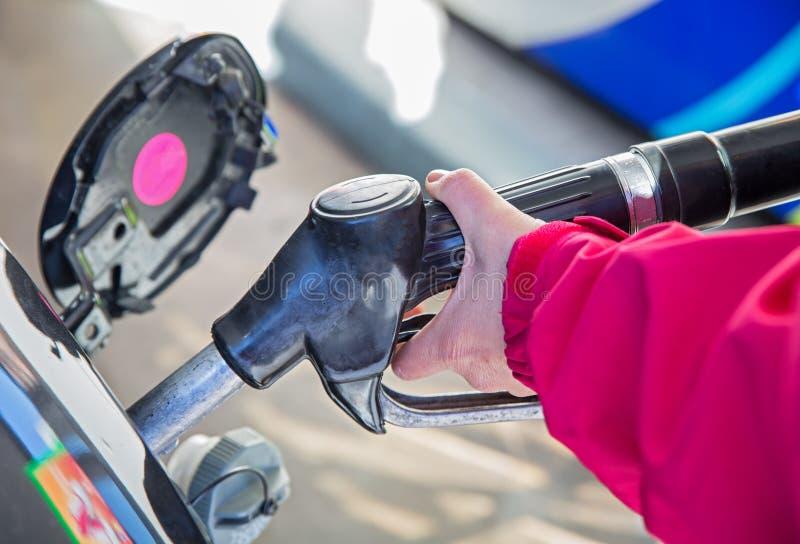 Woman pumping gasoline stock image