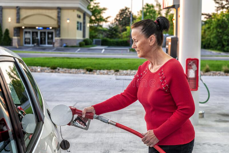 Woman Pumping Gasoline In Early Morning stock photography