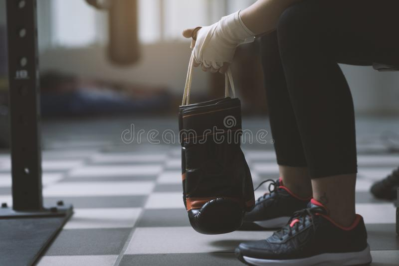Woman with punching gloves resting on a bench royalty free stock image