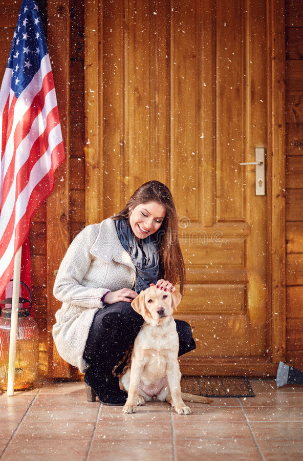 Woman with puppy in front mountain house. Young woman with nice puppy in front mountain house royalty free stock photography