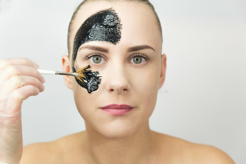 Black mask. Woman with purifying black mask on her face royalty free stock photo