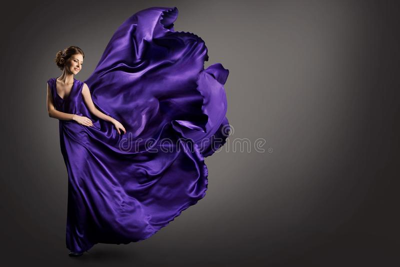 Woman Purple Dress, Fashion Model in Long Silk Gown Waving Cloth on Wind, Fantasy Girl in Flying Fluttering Fabric. Studio shot on gray background stock photo
