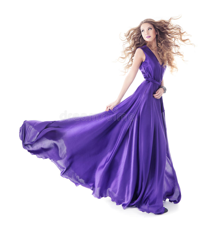 Woman in purple silk waving dress walking over white background stock images