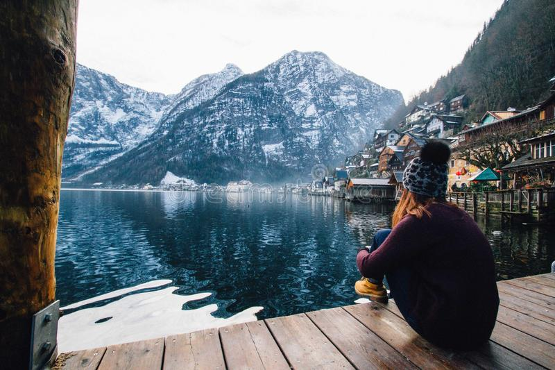 Woman in Purple Sweater Sitting on Wooden Floor With View of Lake and Mountains royalty free stock image