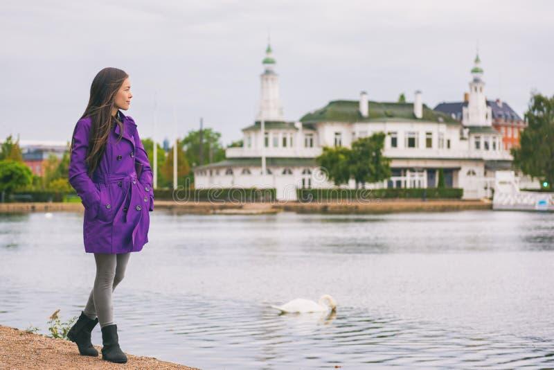 Woman in purple trench coat walking in city park relaxing on weekend. Person enjoying lake view in Copenhagen, Denmark. Spring royalty free stock image