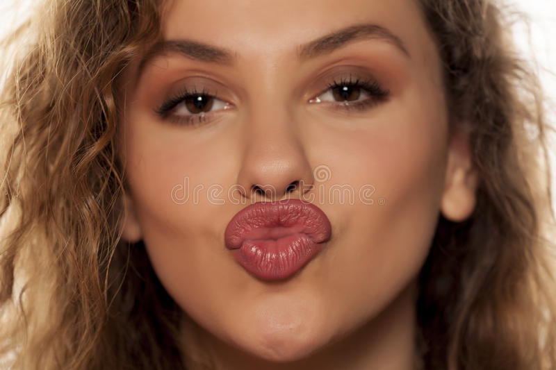 Woman with pursed lips. Beautiful young woman with pursed lips royalty free stock photography