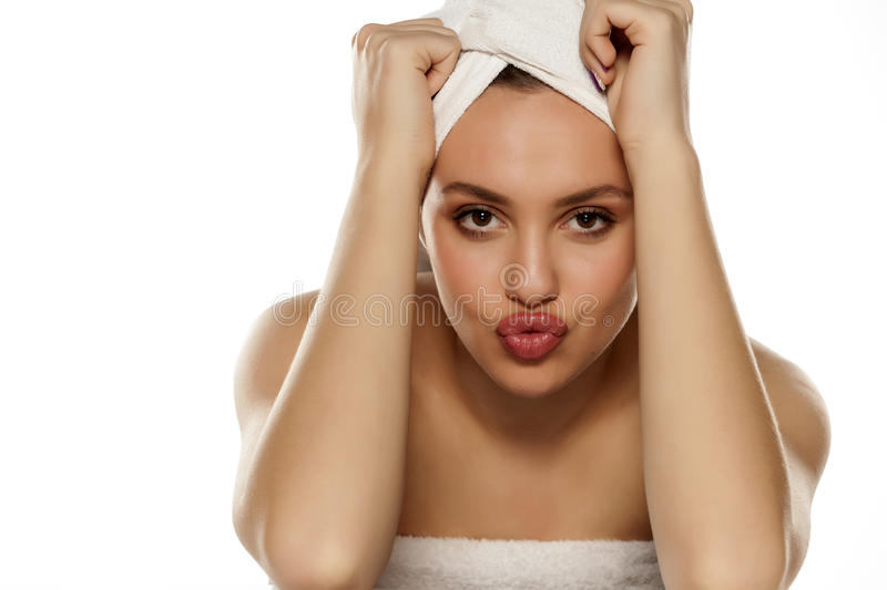 Woman with pursed lips. Beautiful young woman with a towel on her head posing with pursed lips stock images