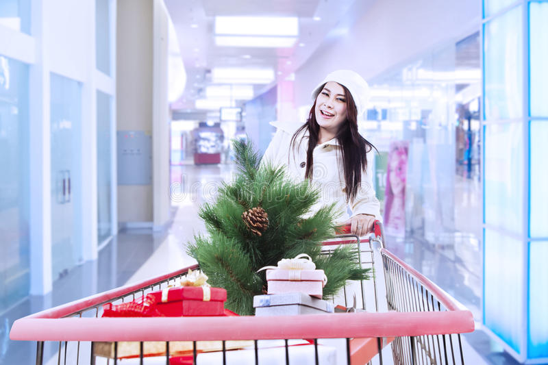Woman push shopping trolley with christmas tree. Woman is shopping for christmas at the mall with trolley royalty free stock photo