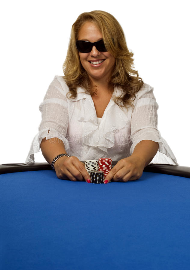 Woman pushes poker chips on blue table stock image