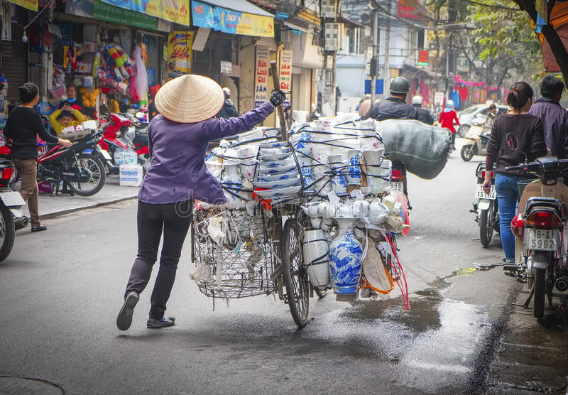 Woman Pushing Bicycle With Wares, Vietnam royalty free stock photography