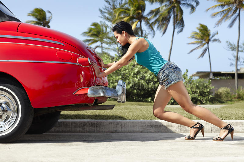 Woman pushing broken down old car. Young hispanic woman pushing broken down red convertible vintage car. Horizontal shape, full length, side view stock photo