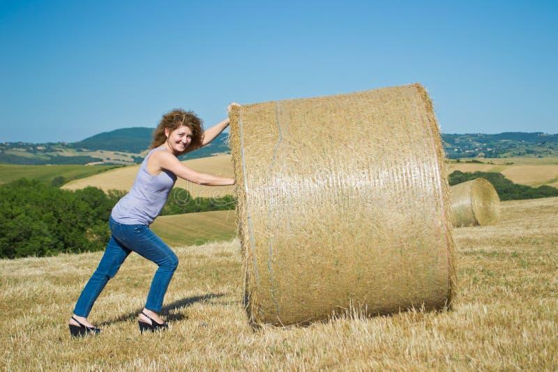 Woman pushing huge bales of hay stock photography