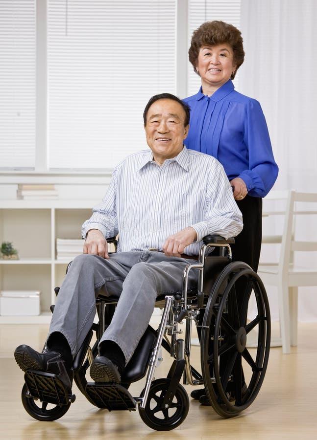 Woman pushing man in wheel chair stock image