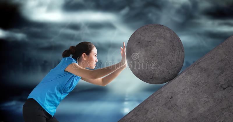 Woman pushing rolling round rock stock image