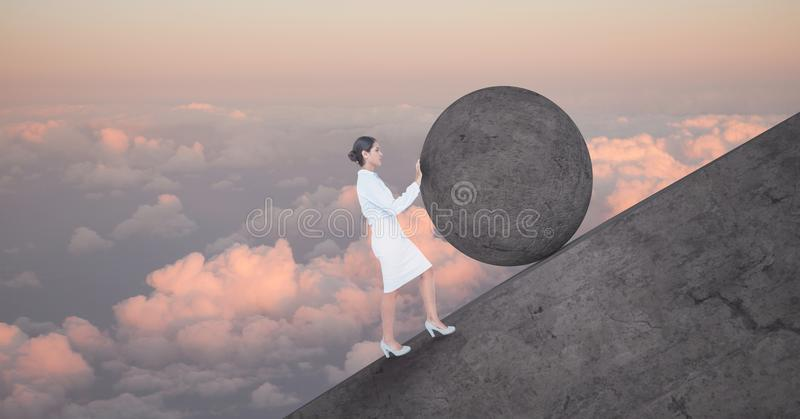 Woman pushing rolling round rock stock photography