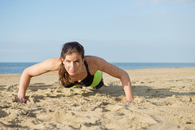 Woman pushing up on a beach royalty free stock image