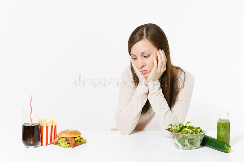 Woman put hands on head with green detox smoothies, salad in glass bowl, cucumber, burger, cola in bottle isolated on royalty free stock images
