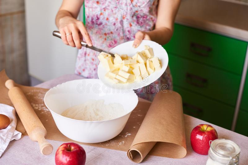 Woman put ingredients for apple pie into big white bowl. Preparing dough in the kitchen royalty free stock images