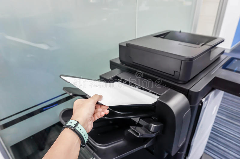 Woman put paper into printer feeder stock photography