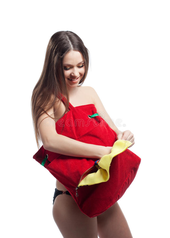 Woman put towel in red beach bag isolated