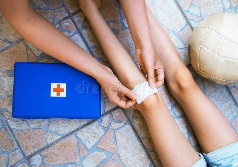 Woman puts adhesive bandage. Woman puts adhesive bandage on child knee royalty free stock photography