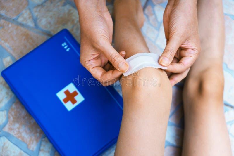 Woman puts adhesive bandage. Woman puts adhesive bandage on child knee royalty free stock image