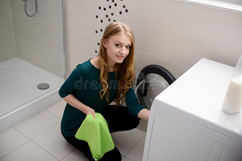 Woman puts dirty laundry into the washing machine stock images
