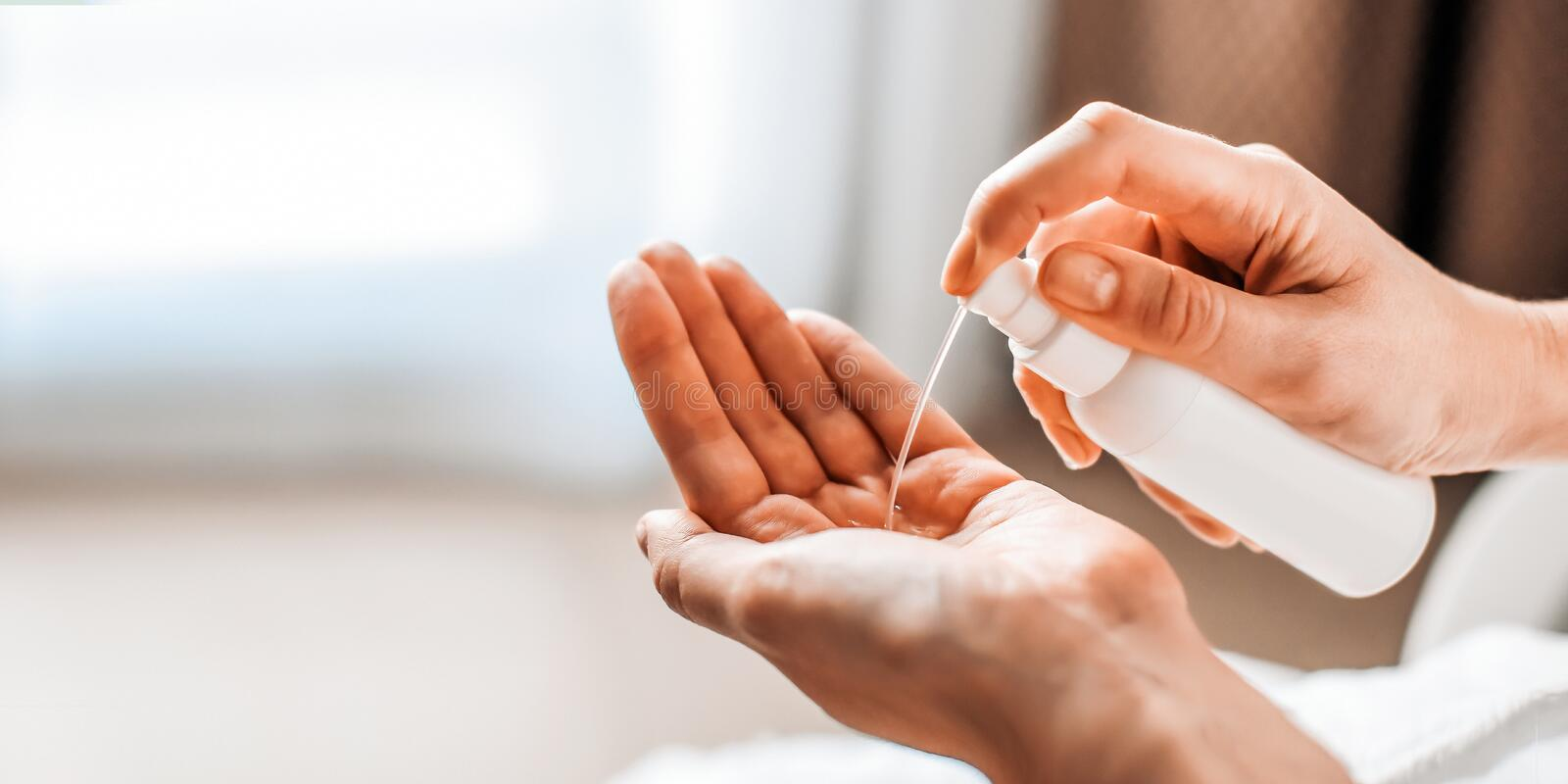 A woman puts on the hands of cosmetics from a bottle or liquid natural soap. Body care concept Banner royalty free stock photography
