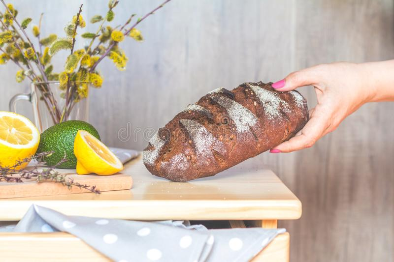 Woman puts homemade rye bread on the table stock photo