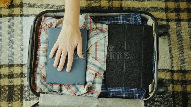 Woman puts a notebook in a travel suitcase royalty free stock images
