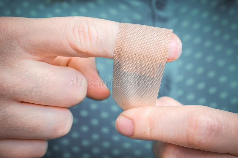Woman puts a plaster on her injured finger stock image