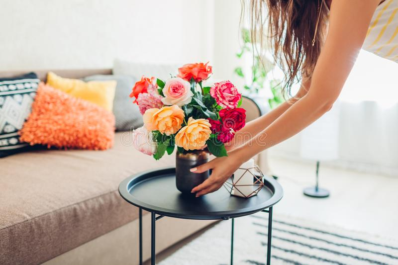 Woman puts vase with flowers roses on table. Housewife taking care of coziness in apartment. Interior and decor stock images