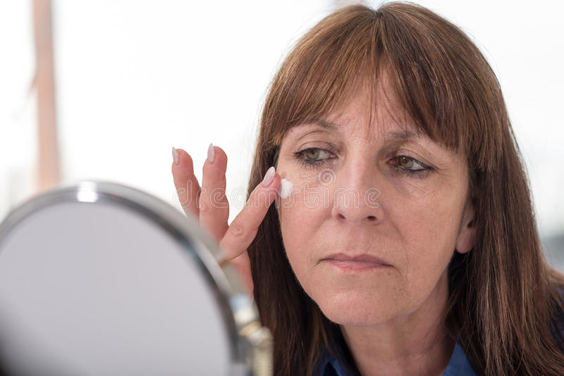 Woman putting anti-age cream on her face stock photography