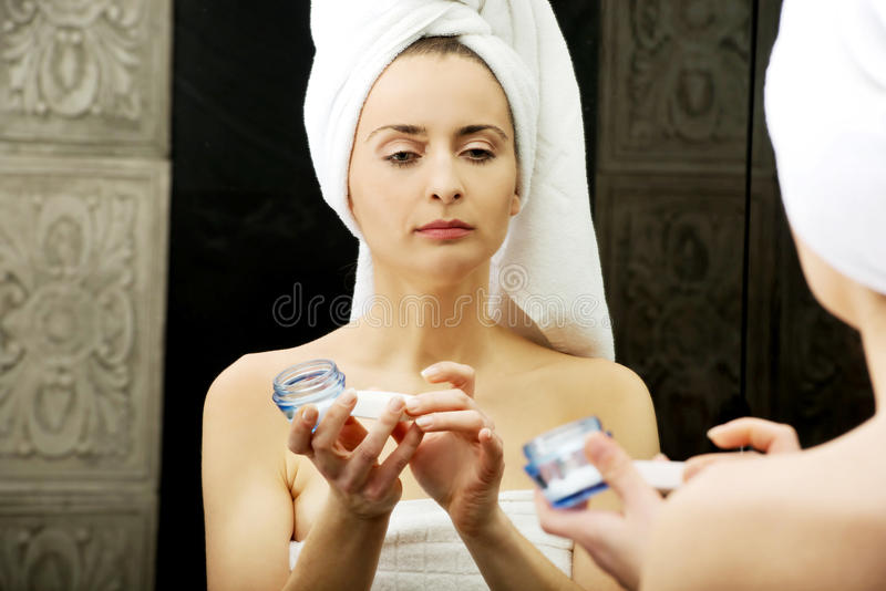 Woman putting anti-aging cream on her face. royalty free stock photos