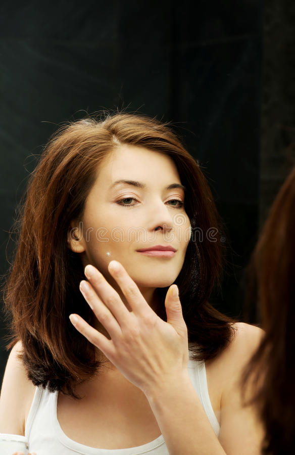 Woman putting anti-aging cream on her face. stock image