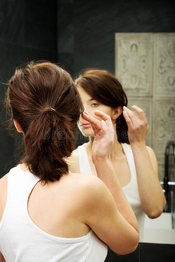 Woman putting anti-aging cream on her face. stock photo