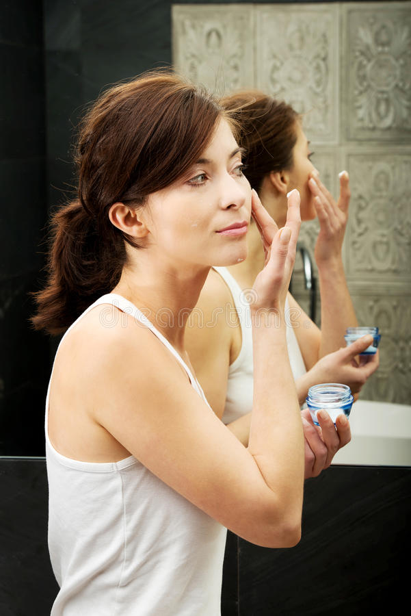 Woman putting anti-aging cream on her face. stock photos