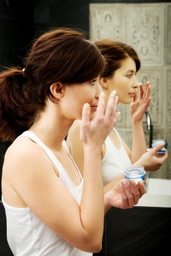 Woman putting anti-aging cream on her face. royalty free stock photo