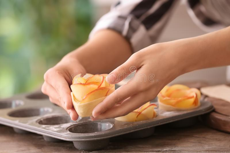 Woman putting apple cake into baking mold in kitchen stock photo