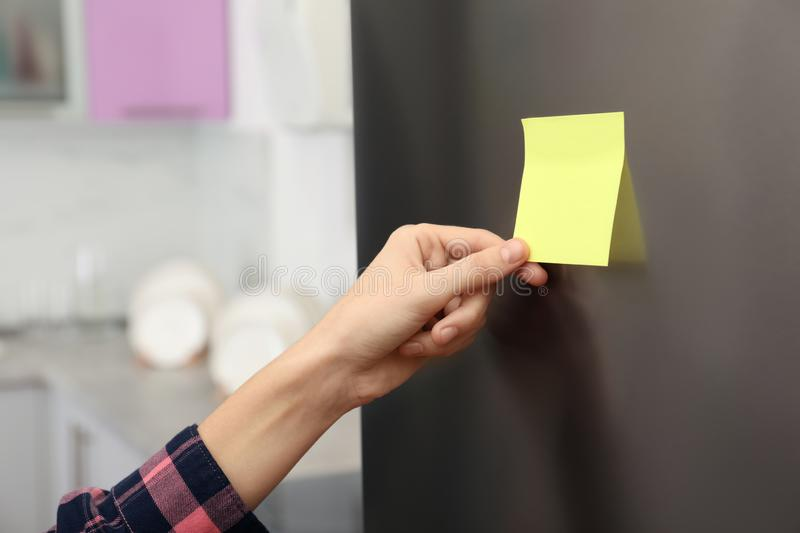 Woman putting blank sticky note on refrigerator door stock photography