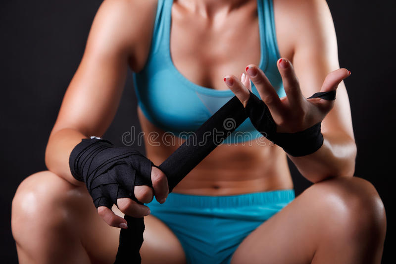 Woman putting boxing bandage on her hands royalty free stock image