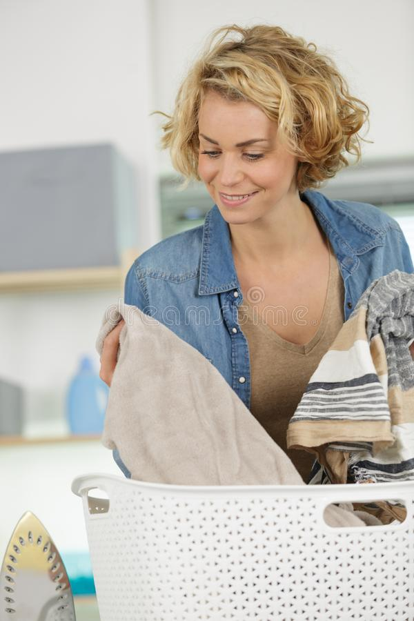 Woman putting clean rolled towels into basket on bed stock photos