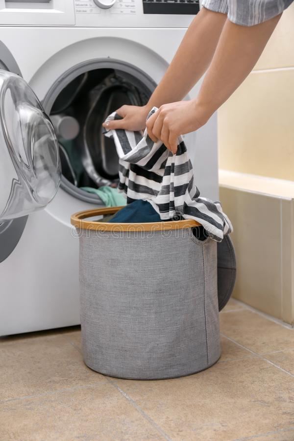 Woman putting clothes into washing machine at home royalty free stock photos