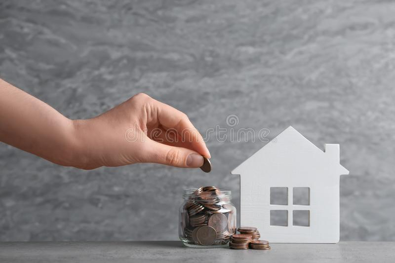 Woman putting coin into glass jar near house model on table against grey background. Space for text stock photo