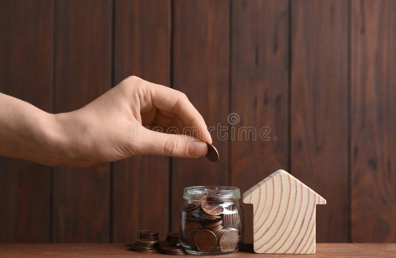 Woman putting coin into glass jar near house model on table against wooden background royalty free stock photo