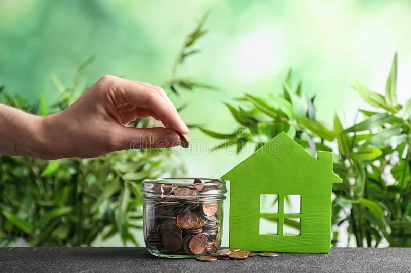 Woman putting coin into jar near house model on table against blurred background. Space for text royalty free stock photo