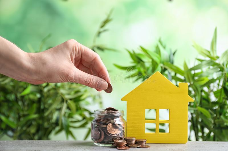 Woman putting coin into jar near house model on table against blurred background. Space for text stock images